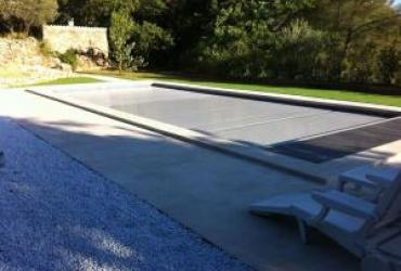 Une piscine traditionnelle en béton de couleur gris foncé dans le var à sollies pont