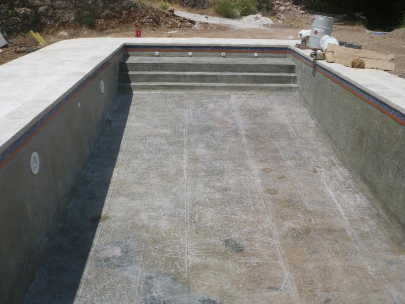 Une piscine traditionnelle en b ton de couleur gris fonc for Construction piscine traditionnelle